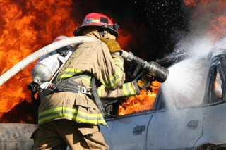 A firefighter hosing down a car or truck that's unstoppable.